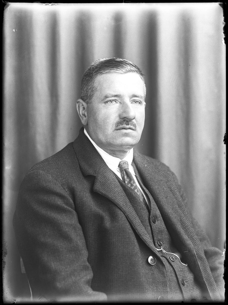 """Porträtt av man i tredelad kostym, slips och klockkedja. I fotografens egna anteckningar står det """"Leonard Håkansson"""". Tolkat som Herman Leonard Håkansson."""
