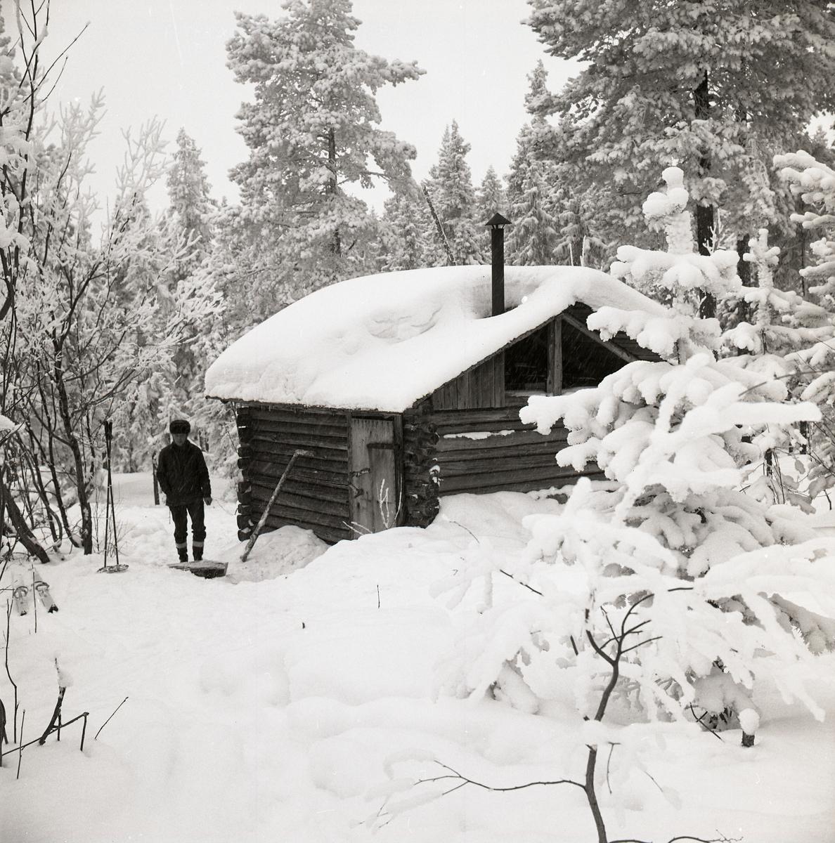 En man står utanför en snötäckt koja i skogen vid Hälsen den 24 februari 1970.