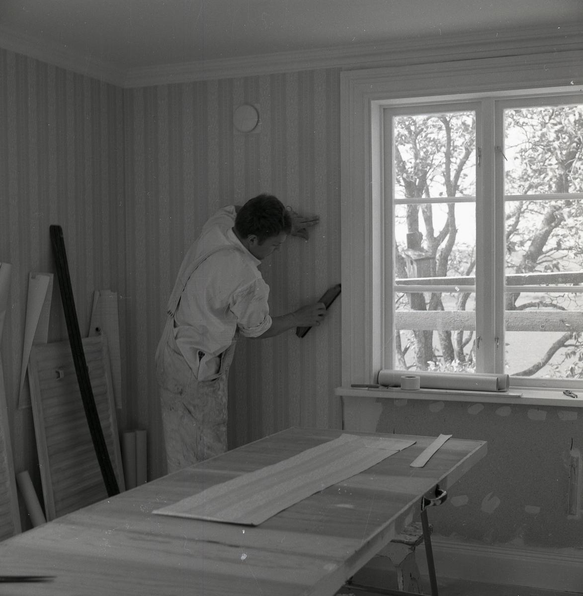 En man tapetserar väggen i ett hus, juni 1968.