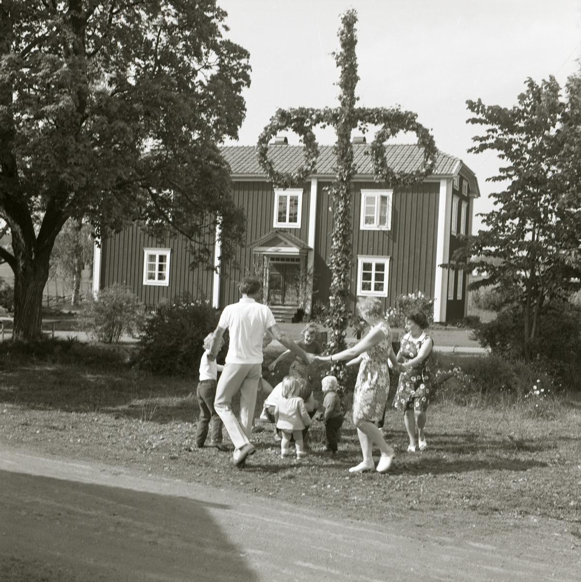 En grupp människor dansar omkring midsommarstången vid gården Sunnanåker, 1971.