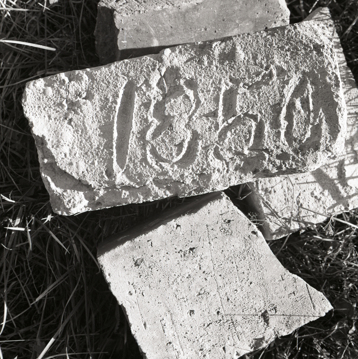Några tegelstenar ligger i gräs och på den ena är inristat årtalet 1850, Rengsjö 1967.