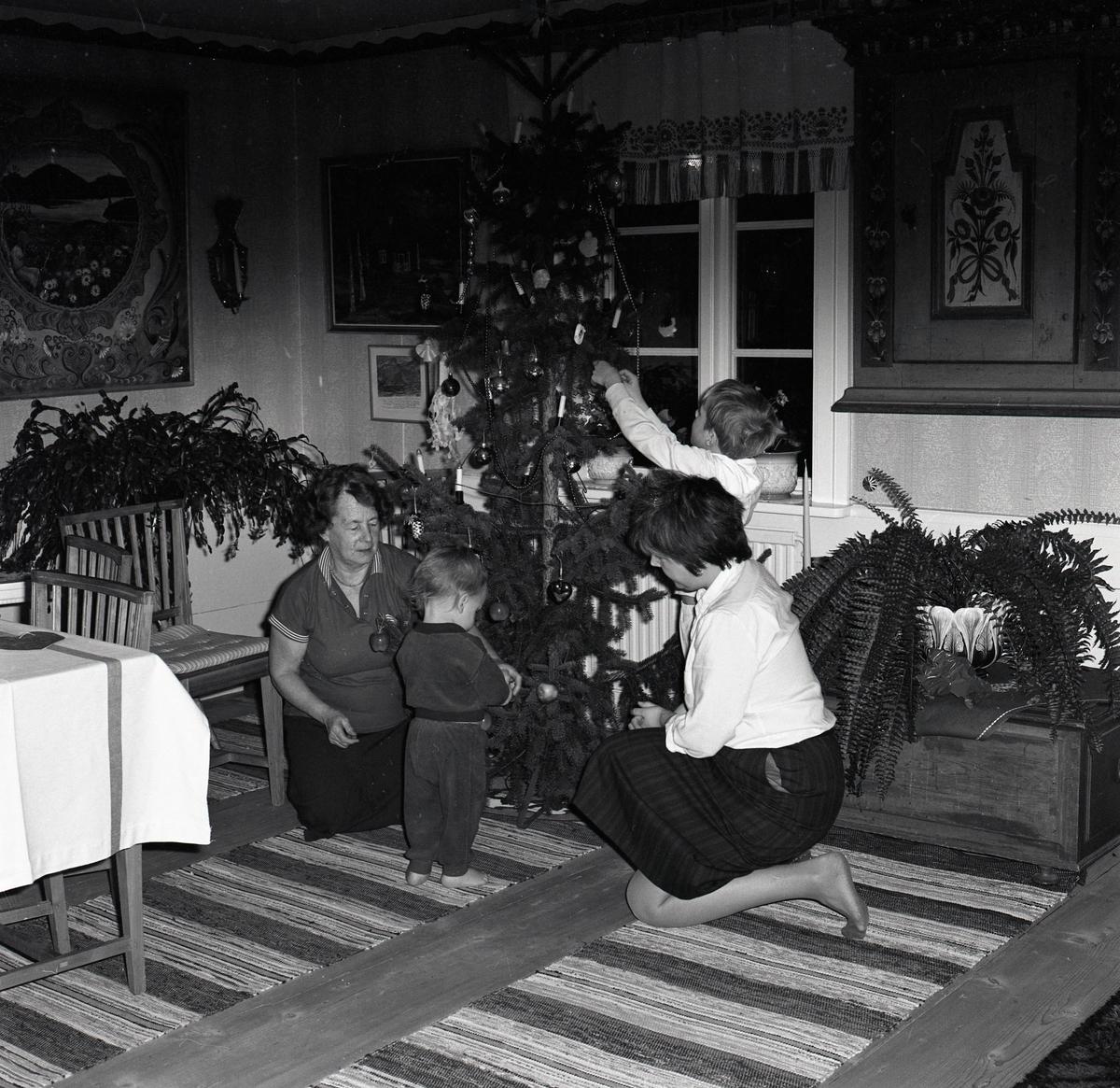 Två kvinnor och två barn klär en julgran den 21 december 1985.