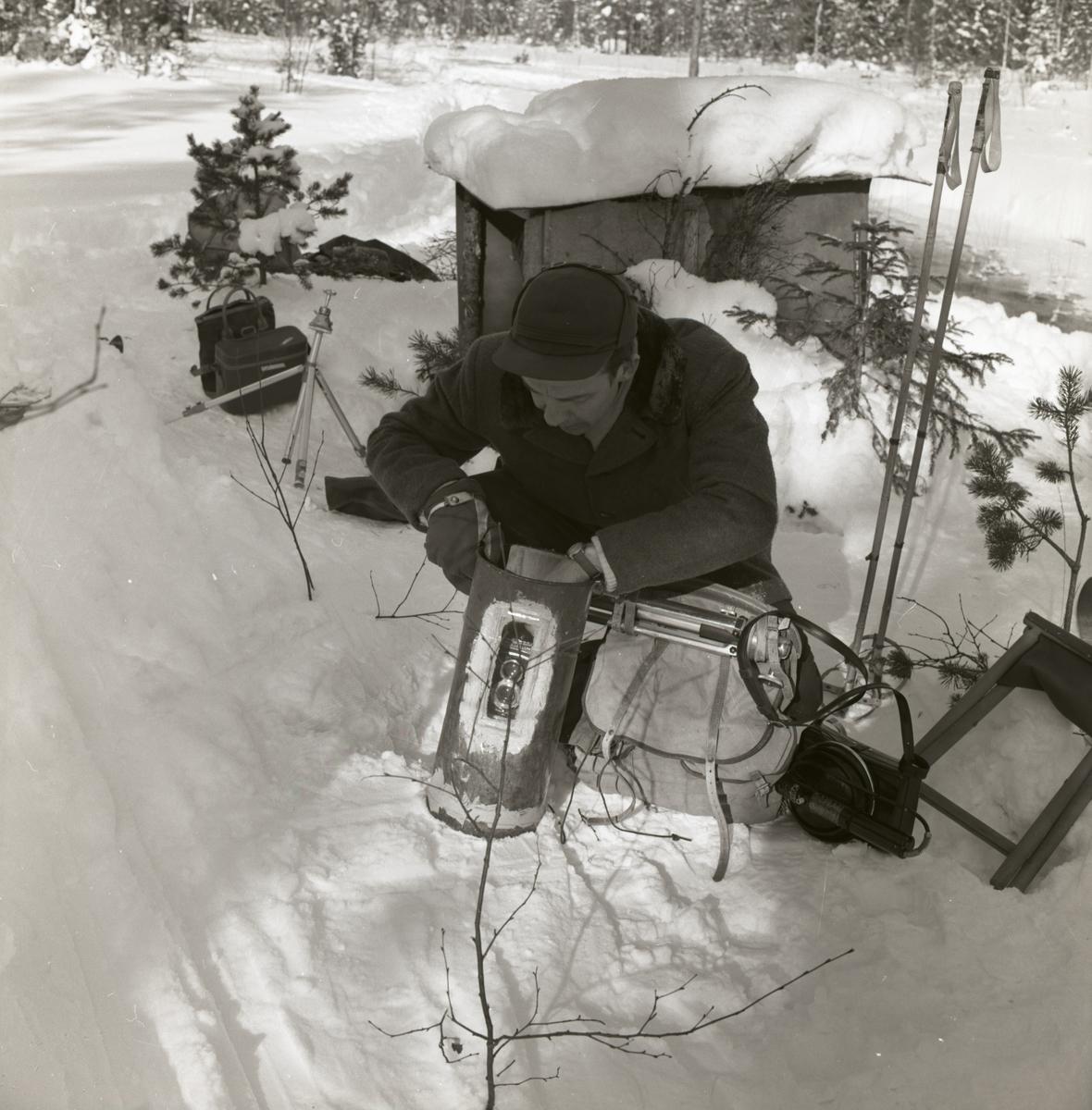 En man riggar fotoutrustning, sittandes på huk i snön, 1962.