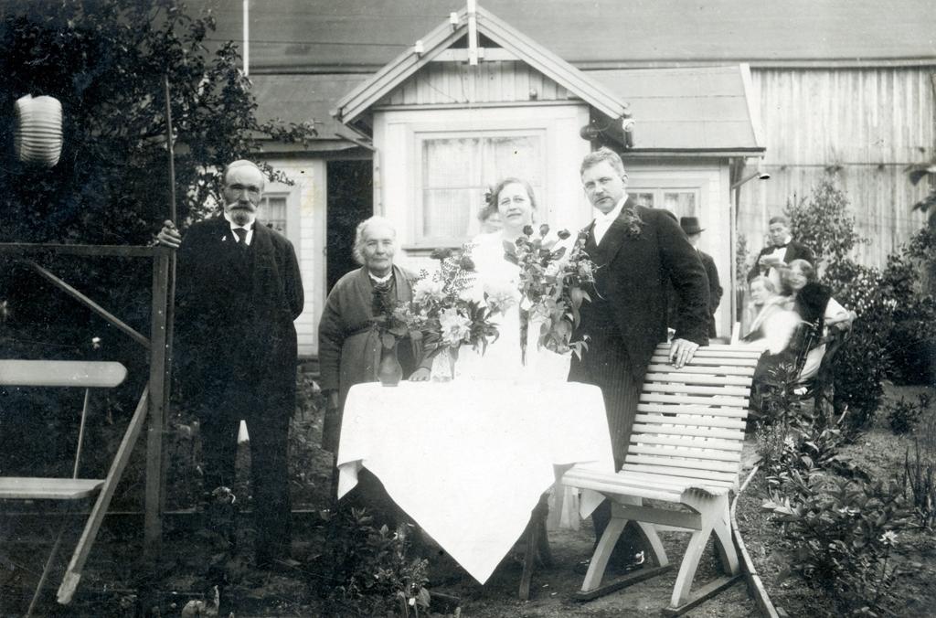 Alfred Träff och hans fästmö vid deras förlovningsfest. Paret står tillsammans med ett äldre par runt ett bord med buketter i en trädgård. Bakom dem synd ett hus och flera personer.