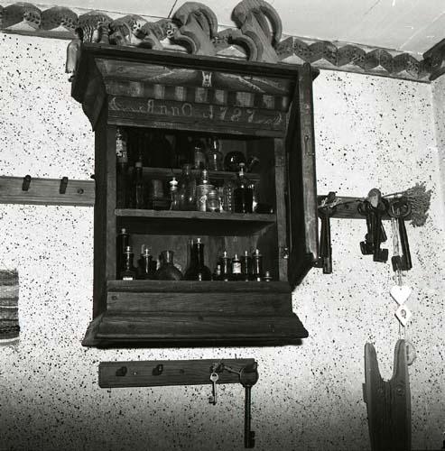En interiörbild från gården Sunnanåker med ett väggskåp på en stänkmålad vägg, 1984.