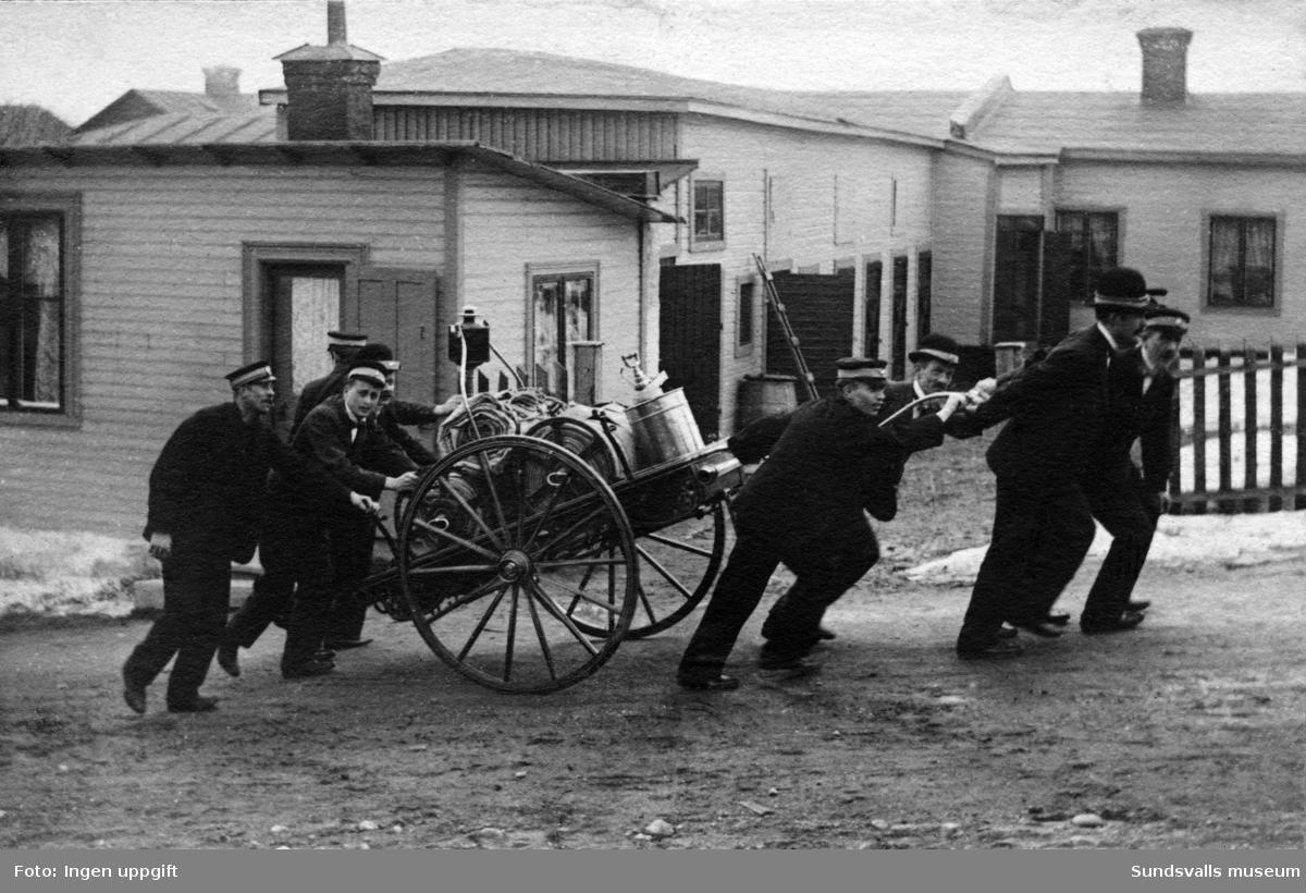 Brandmän som drar en brandvagn upp för en brant backe, troligen Södermalm. Ur album från brandchefen för Sundsvalls brandkår Gustaf Hellgren och hans familj.