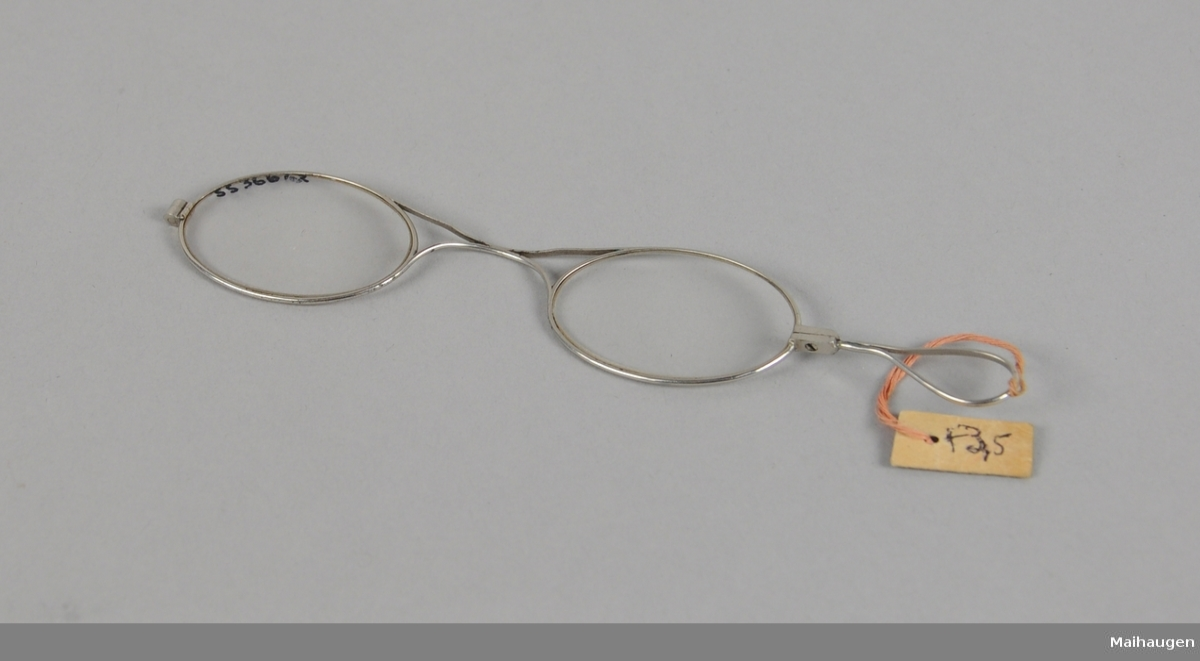 Ovale brilleglass i metallinnfatning. Metallhempe på den ene brillen. Brillen ligger i en plastemballasje