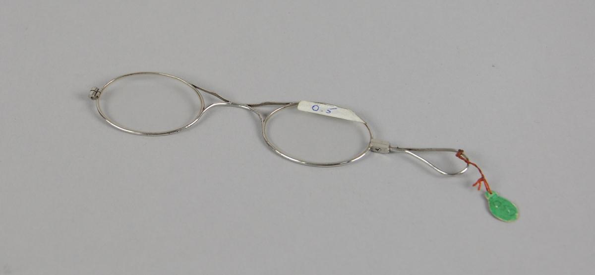 Ovale briller med metallinnfatning. Det er en hempe på den ene siden av brilleglassene.