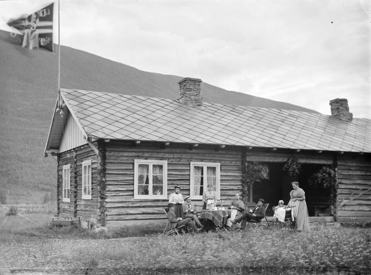 """I protokollen står det """"Kontorist Monsen og Rask"""". Enetasjes tømmerbygning med en gruppe mennesker og norsk flagg. Flagget har bokstaver påskrevet."""