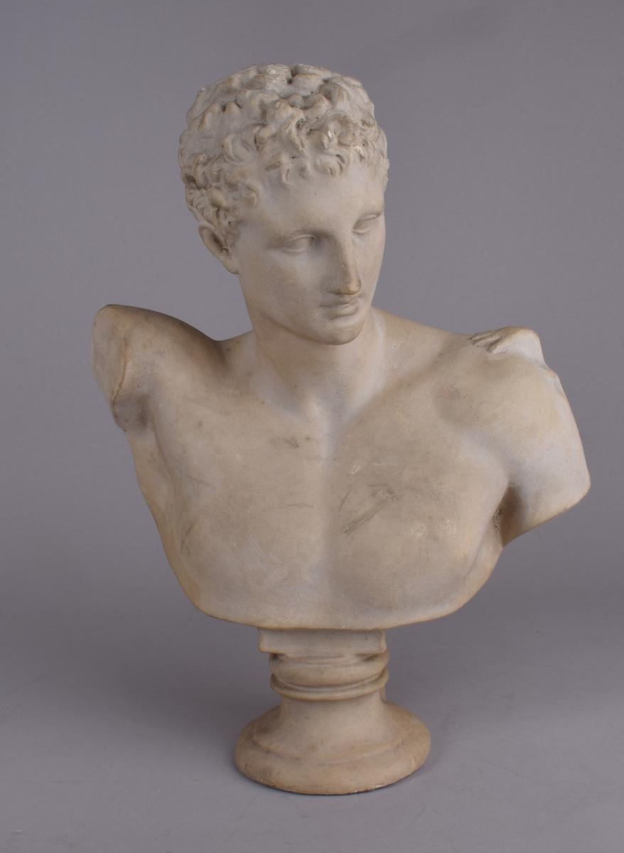 Klassisk mannsfigur med bølget kort hår.