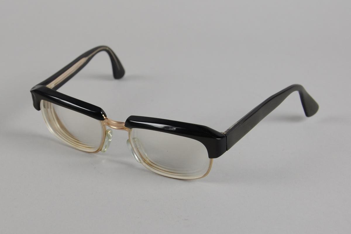 Firkantede brilleglass med avrundede kanter. Metallinnfatning med svart plast på oversiden av brilleglassene. Brillestengene er også forsterket med svart plast.