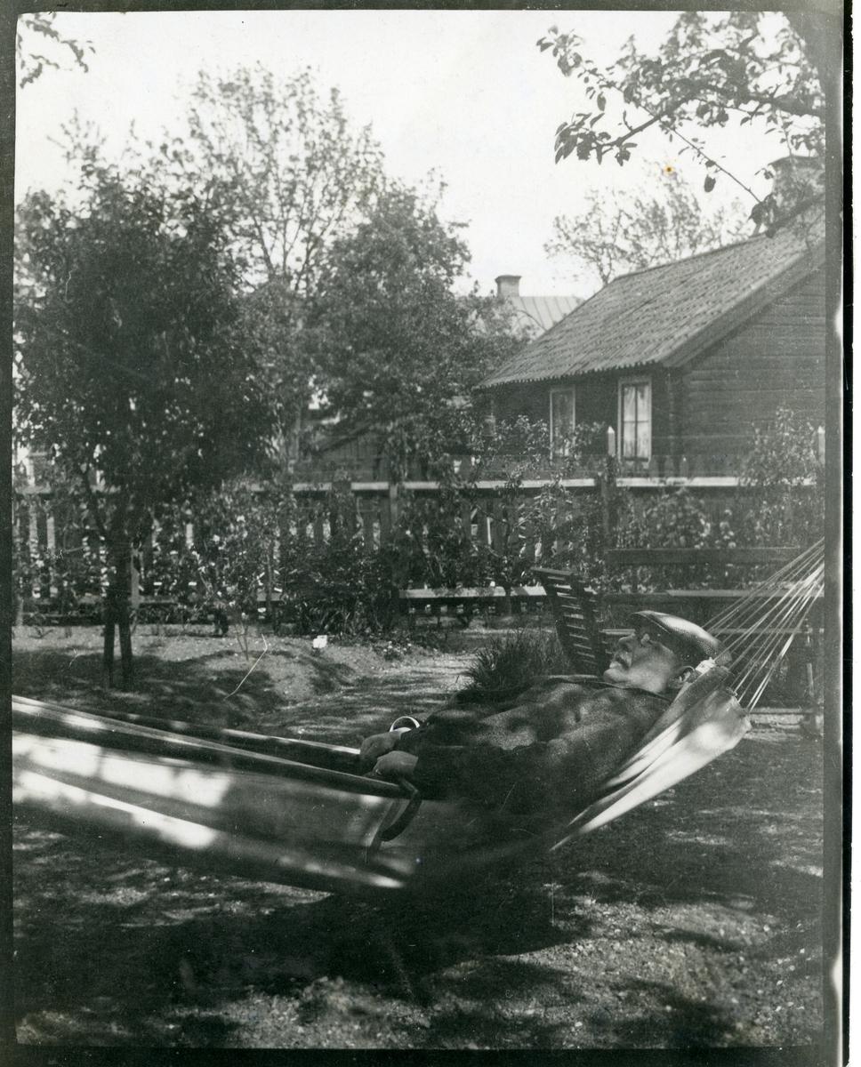 Nymans ur. Urmakaren Adolf Nyman i hängmatta i sin trädgård som utgjorde norra delen av hans omkring år 1902 förvärvade fastighet Stora gatan 26 A - den s.k. Porathska gården. (Adolf Nyman föddes i Almtuna 21/6 1853 och avled i Västerås  23/12 1926).  Kv. Lennart i Västerås.