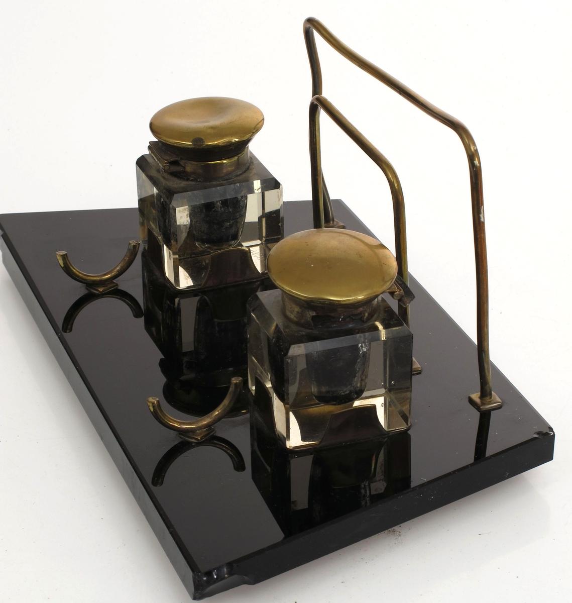 Trapesformet plate av sort glass, hvorpå festet messingholdere med blekkhus av kubiskslepet krystall.  Beslag og lokk av messing. To messingbøyler for brev, samt to ditto for henleggelse av penn.