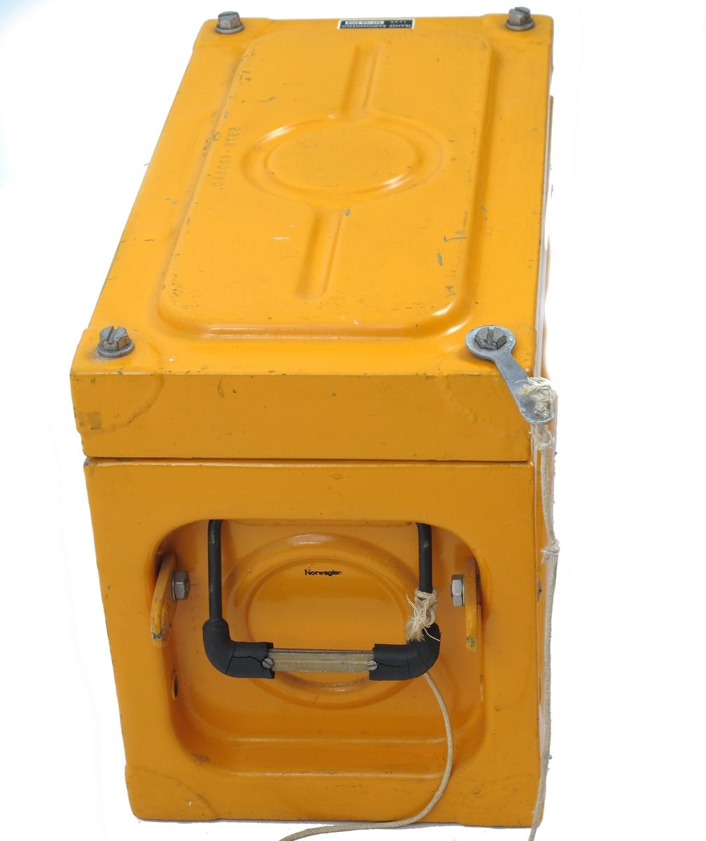 Radiosender pakket i solid emballasje, beregnet for lagring i livbåter. Gulfarget  kasseformet beholder med lokk festet med fire muttere. Bærehandtak med gummibelegg i begge ender, samt beslag for fastskruing. Gummibelegg på handtak ødelagt. Mutternøkkel festet i snor til kassen.