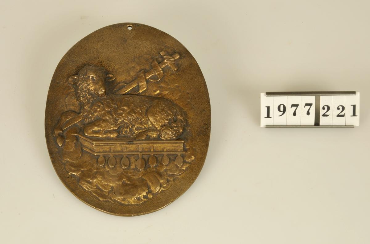 Oval form. Motiv: Guds lamm, vilande på moln.  Storlek: 10,2 x 13,0 cm.