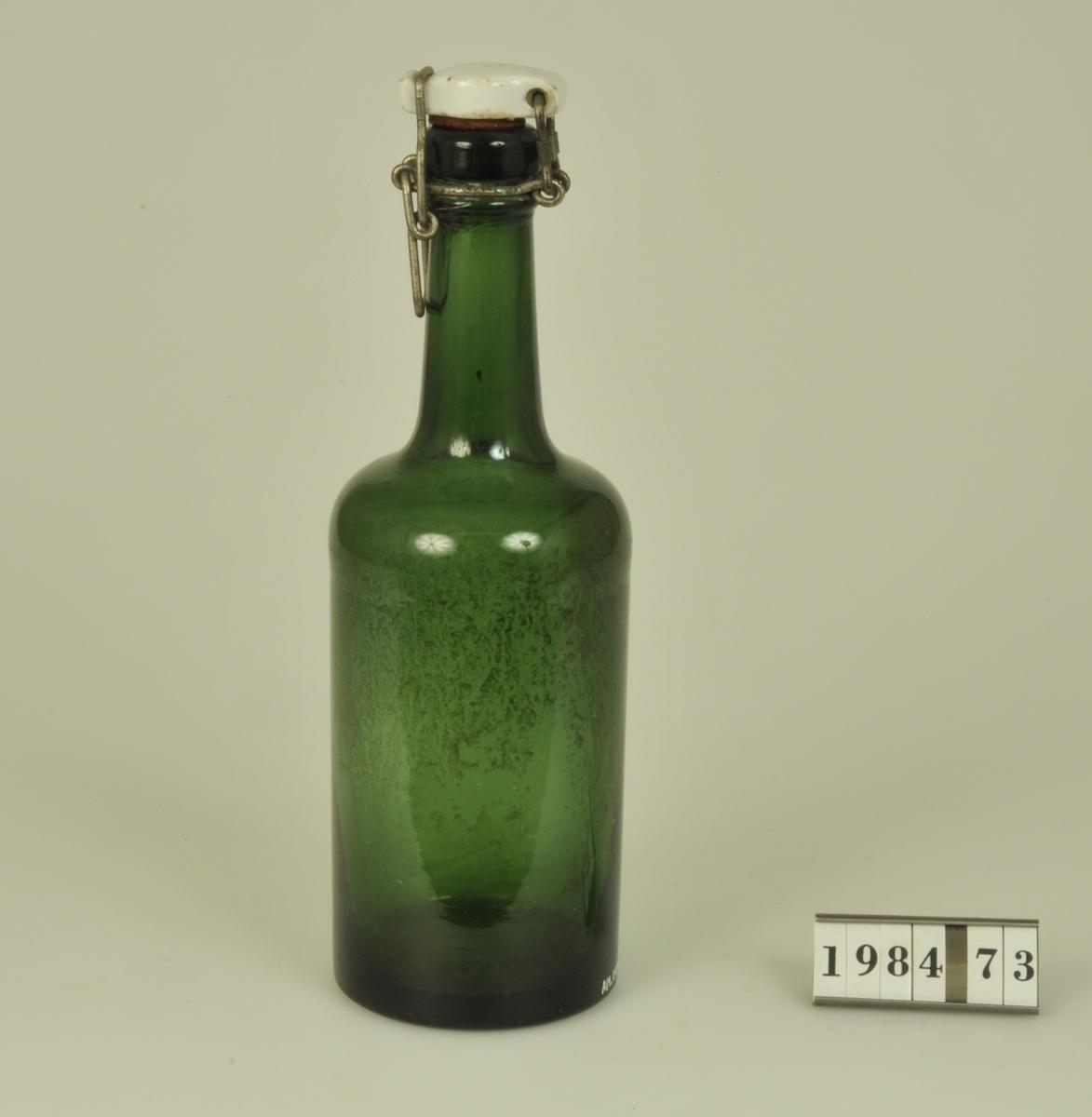 Butelj av grönfärgat glas med kapsyl av vitt porslin.  Okänd anknytning.