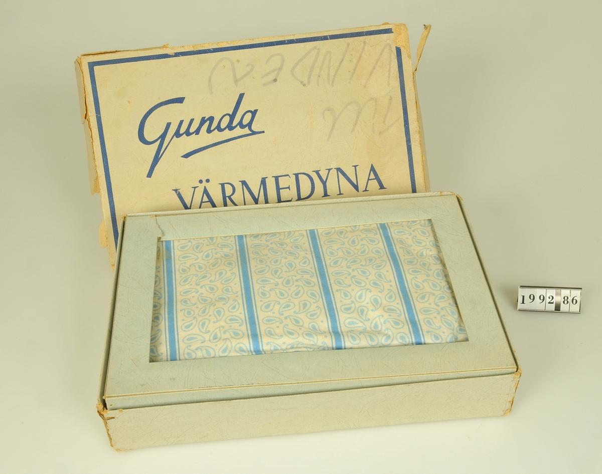 För elanslutning.  Termostat, strömställare för tre värmelägen, S-märkt.  Klädd med mönstrat bomullstyg (blått tryck på vit botten.)  Förvaras i originalförpackningen (storlek: 315 x 215 mm.)  Använd i givarens föräldrahem.