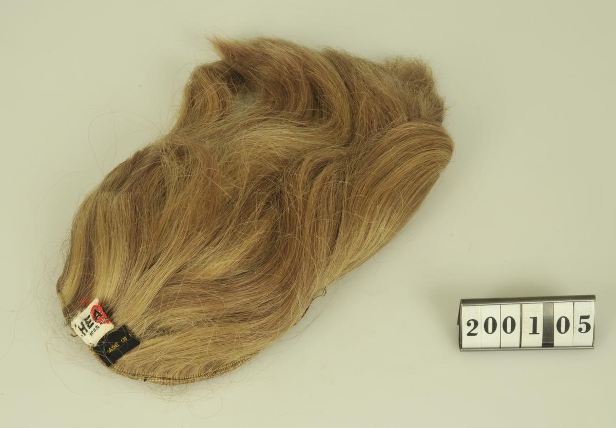 Av blont hår. Funktion: För utfyllnad av frisyrer och håruppsättningar