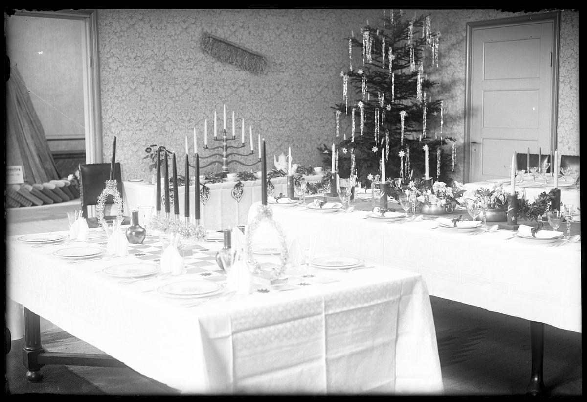 Exempel på juldukningar visas på Husmodersföreningens julmässa. Fyra bord med linnedukar och porslin står uppställda och i rummets ena hörn står en julgran.