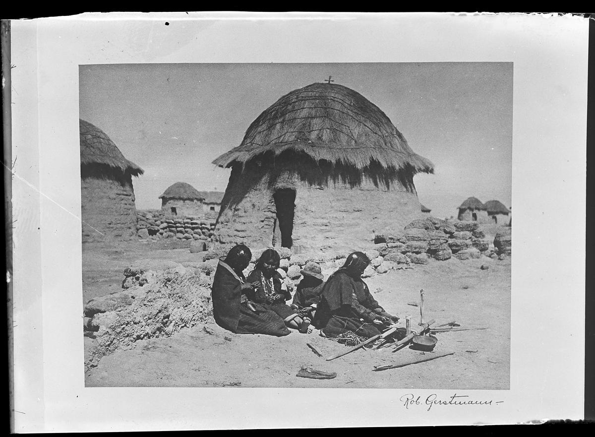 """Tre kvinnor och ett barn sitter och arbetar framför en mur. På andra sidan muren syns ett antal byggnader. Bilden är signerad Rob. Gerstmann och reprofotograferad av Harald Olsson. I Olssons anteckningar står det """"27 rep. för Folke Olsson""""."""
