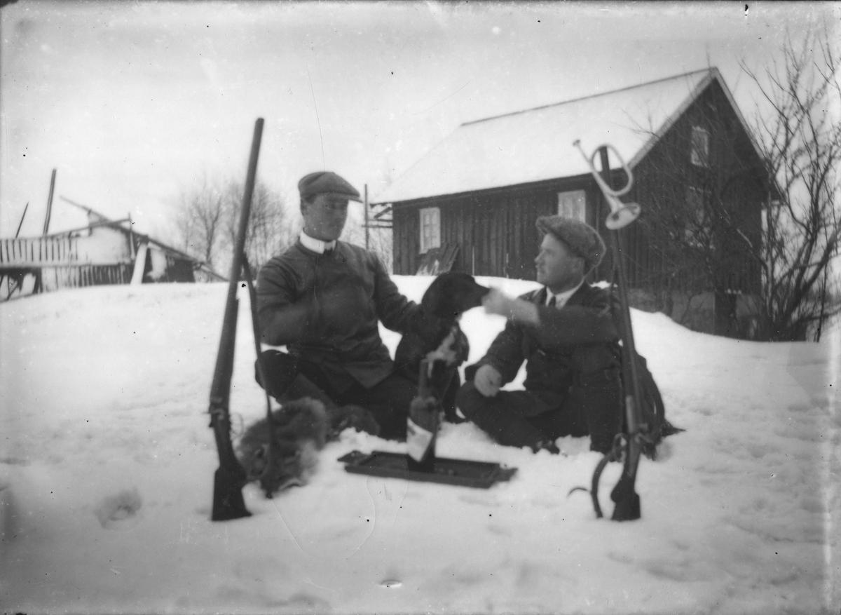 Två män med jaktbyte och gevär samt ett jakthorn vintertid.