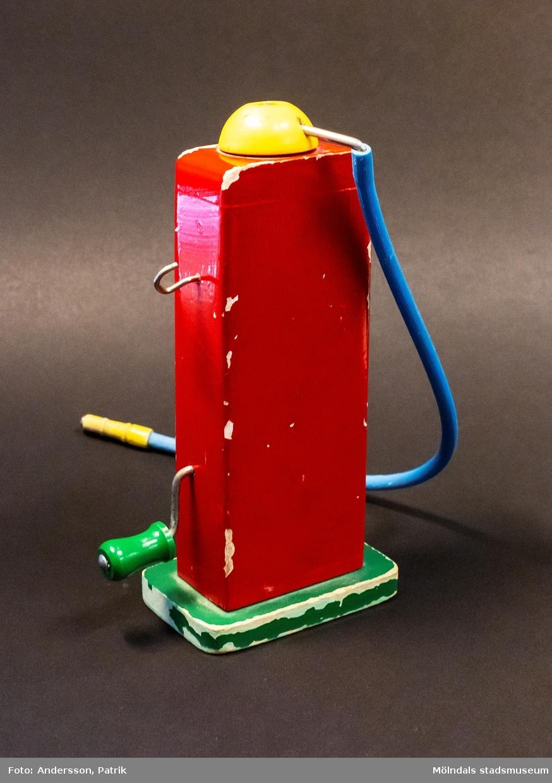 Esso bensinpump i trä. Något sliten. Pumpen är röd och står på en grön platta. Överst på pumpen sitter en gul roterbar knapp och från den löper en blå gummi-slang att tanka med. Fronten är vit och på den nedre delen ses Esso-logon (blå-vit-röd) och på ovandelen ses en blåmålad liter-ruta (0 - 90 liter) med en gul visare i mitten. Visaren är sammankopplad med en vev som sitter på pumpens högra sida i höjd med Esso-logon och som går att snurra på. Ovanför veven sitter en krok att hänga gummi-slangen på. Tillverkad av Brio. Inköpt av givaren år 1970 i Mölndals leksaksaffär på Kungsbackavägen och användes av sönerna Anders (född 1970) och Mathias (född 1973).