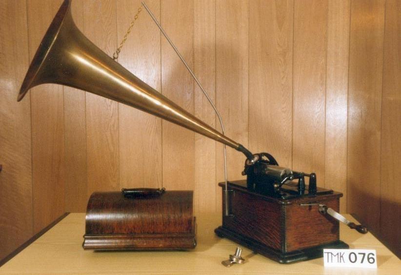 """Sveivefonograf. Edison Standard modell B nr. 661684. Modellen ble kalt """"The Tall Standard"""" fordi den var litt høyere enn tidligere modeller. Lydhodet er en Edison modell C nr. A 46983 2. Fonografen var oppprinnelig laget for av- og innspilling av 2 minutters sylindere, men fikk senere originalt tilleggsutstyr for avspilling av 4 minutters sylindere med lydhodet Edison modell H nr. A 509177. Dette tilleggsutstyret kom på markedet i 1908. Motoren er sveivetrukket og har en fjær.   Kassen er i brun eik med buet, avtagbart lokk. Bunnen er lakkert mørkere enn resten av kassen. Rundt selve fonografen går en dobbel gullbord med ornamentikk i hjørnene. På fonografens forside er det montert et oppheng til hornet. Hornet er av messing og er laget i ett stykke uten falsing."""