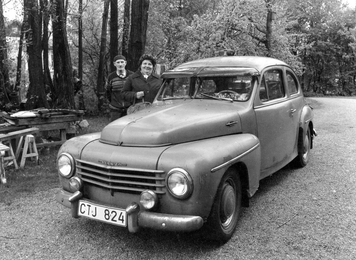 """Främst på bilden syns en Volvo PV 1952, registreringsnummer CTJ 824, parkerad vid """"Åhyddan"""", kv Fregatten 4. Bakom bilen står en man klädd i basker och en kvinna."""