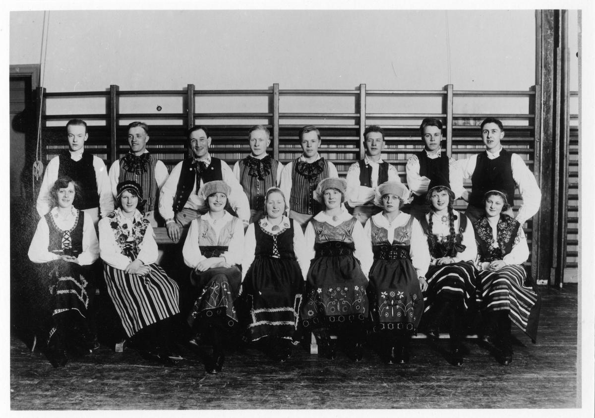 Gruppbild av Alingsås folkdanslag. Bilden är tagen i en gymnastiksal och föreställer 8 kvinnor (sittande) och 8 män (stående) klädda i olika folkdräkter.