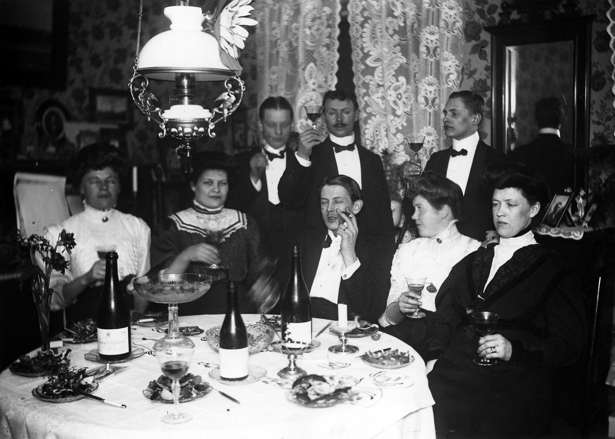 En grupp män och kvinnor samlade vid ett festdukat bord.