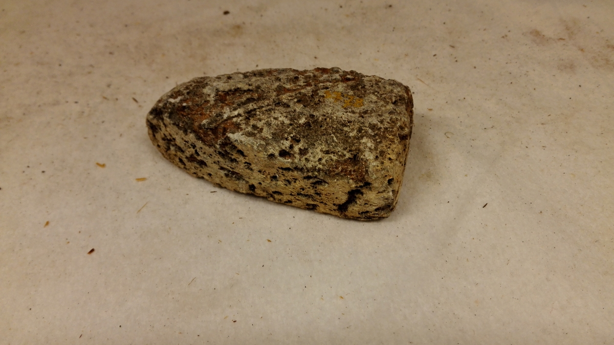 1 strykejernsbolt av klæbersten  Liten løsbolt for strykejern. Man hedet bolten i varme og stak den i strykejernet, som derved blev ophedet. Tykkelse 2,7 cm, længde 9,5 cm og bredde 6 cm. Kjøpt av gaardbr. Bjørn K. Gjeithus, Arnefjord.