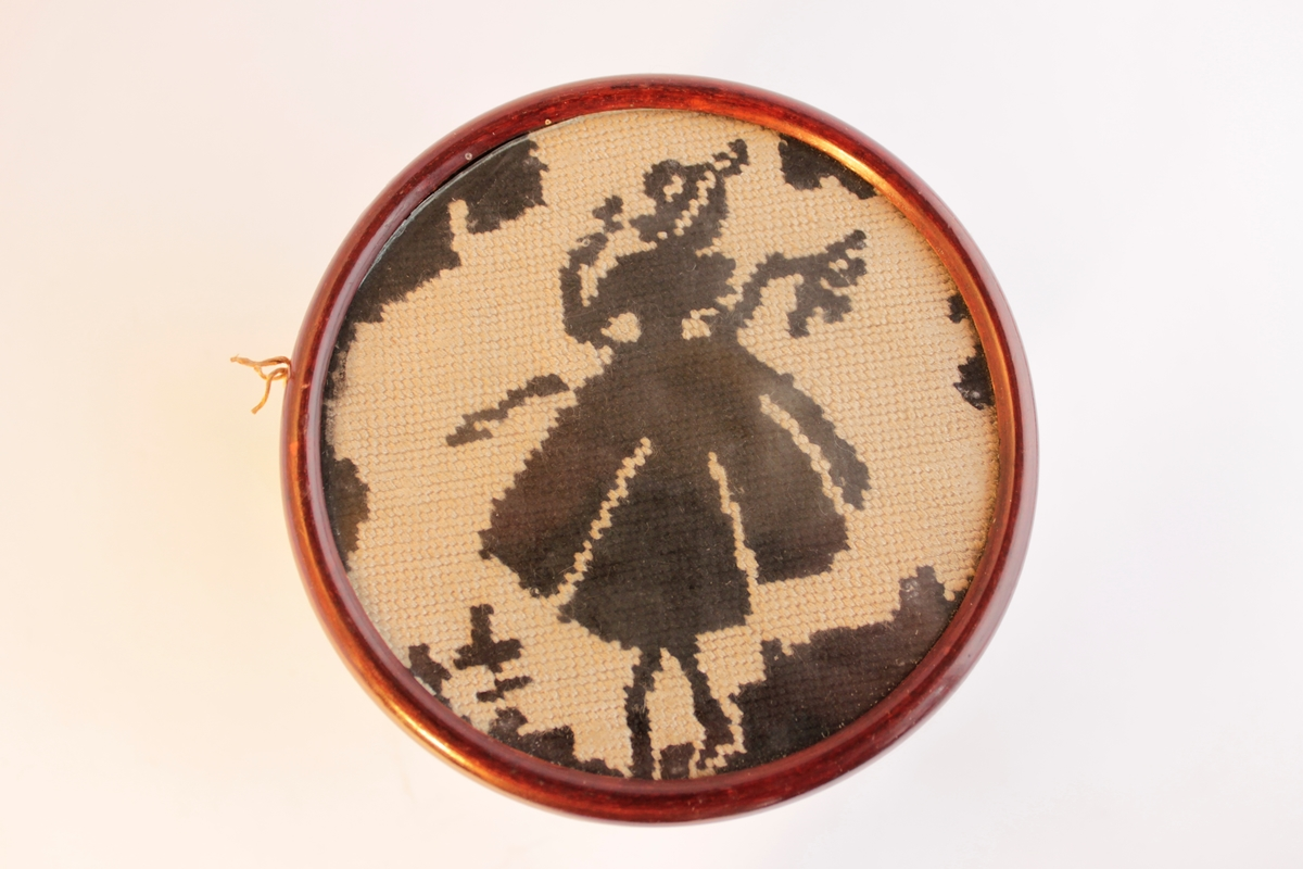 Inramat broderi med mahognyfärgad träram. Broderat med tekniken petit points. En svart figur mot en ljus bakgrund. Motivet föreställer en dansande flicka.