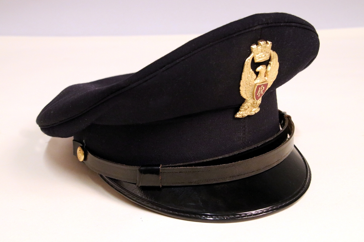 Mørk blå politilue med sort lakkskjerm og gull merke med rød detalj.