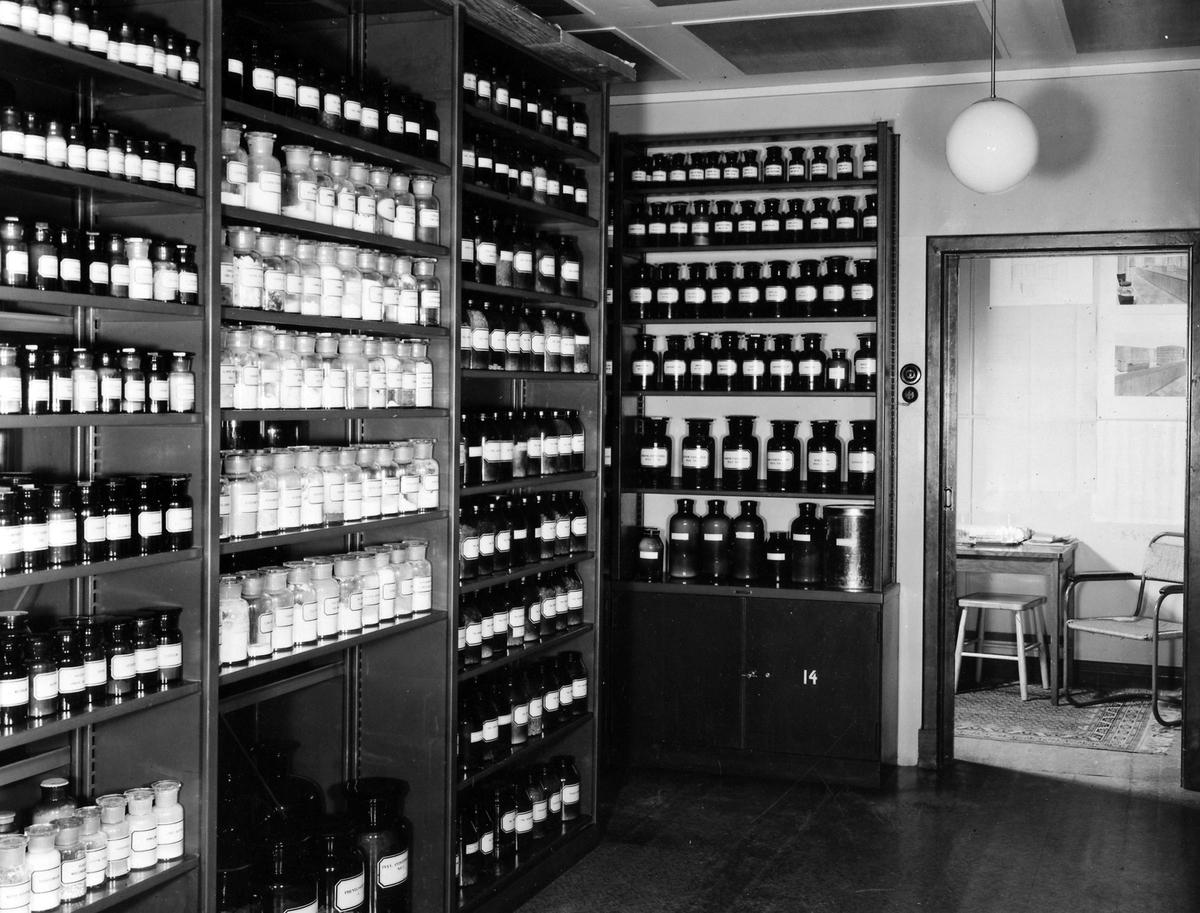 Materialkammaren på apoteket Hjorten. Bilden visar vänstra väggen fylld från golv till tak av hyllor med flaskor i alla storlekar samt en dörröppning till ett rum med bord och stol.