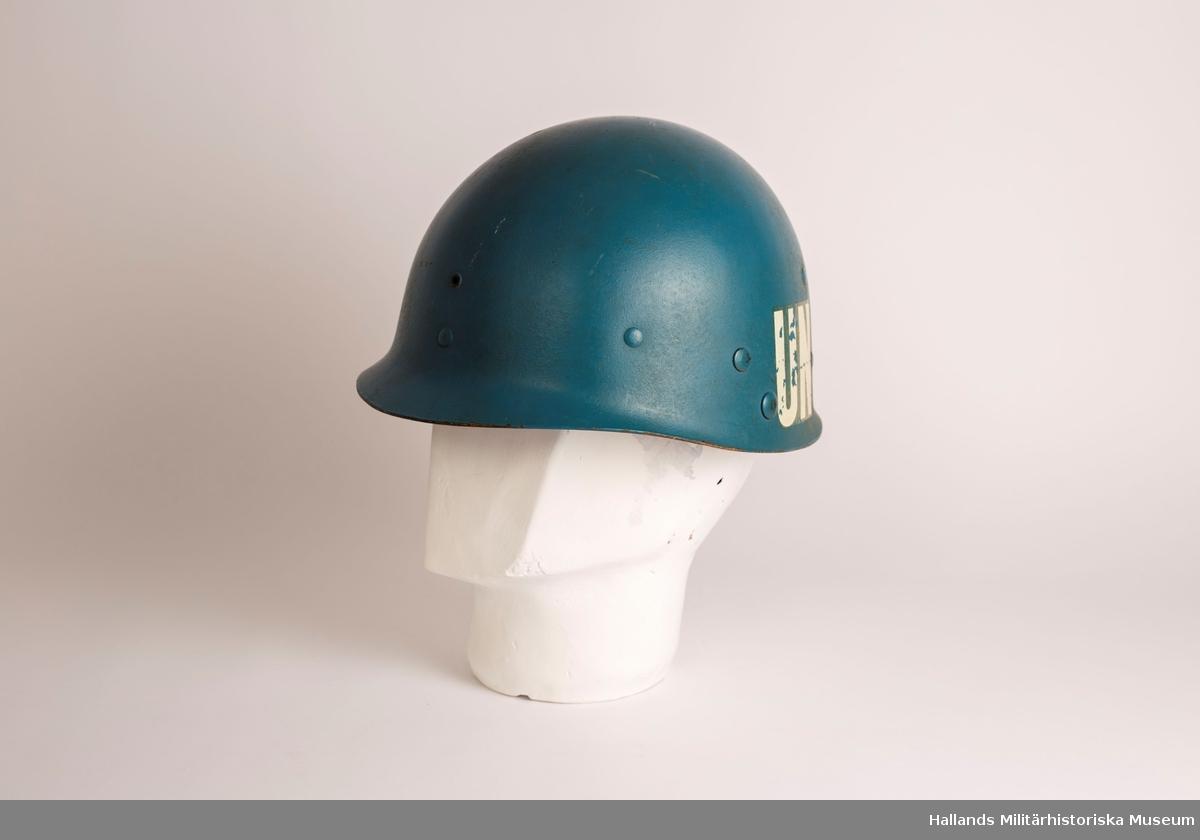 En lätt hjälm av glasfiberarmerad polyester, ljusblå. På båda sidor finns beteckningen UN med vita bokstäver. Den har elva blåmålade nitar som håller fast inredningen som är tillverkad av djungelgröna bomullsband och av ljust läder. Hakbandet är av brunt läder.
