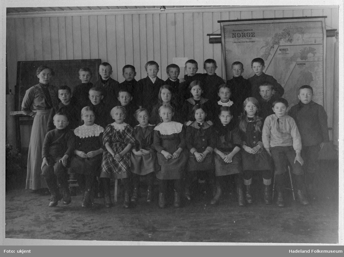 Skolebilde Lundby skole. Elever og lærerinne oppstilt i klasseværelse foran norgeskart.