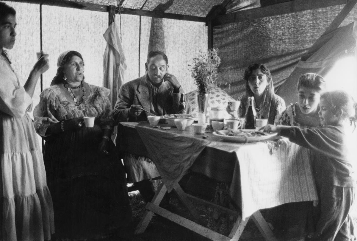 En grupp romer sitter kring ett bord och dricker kaffe.