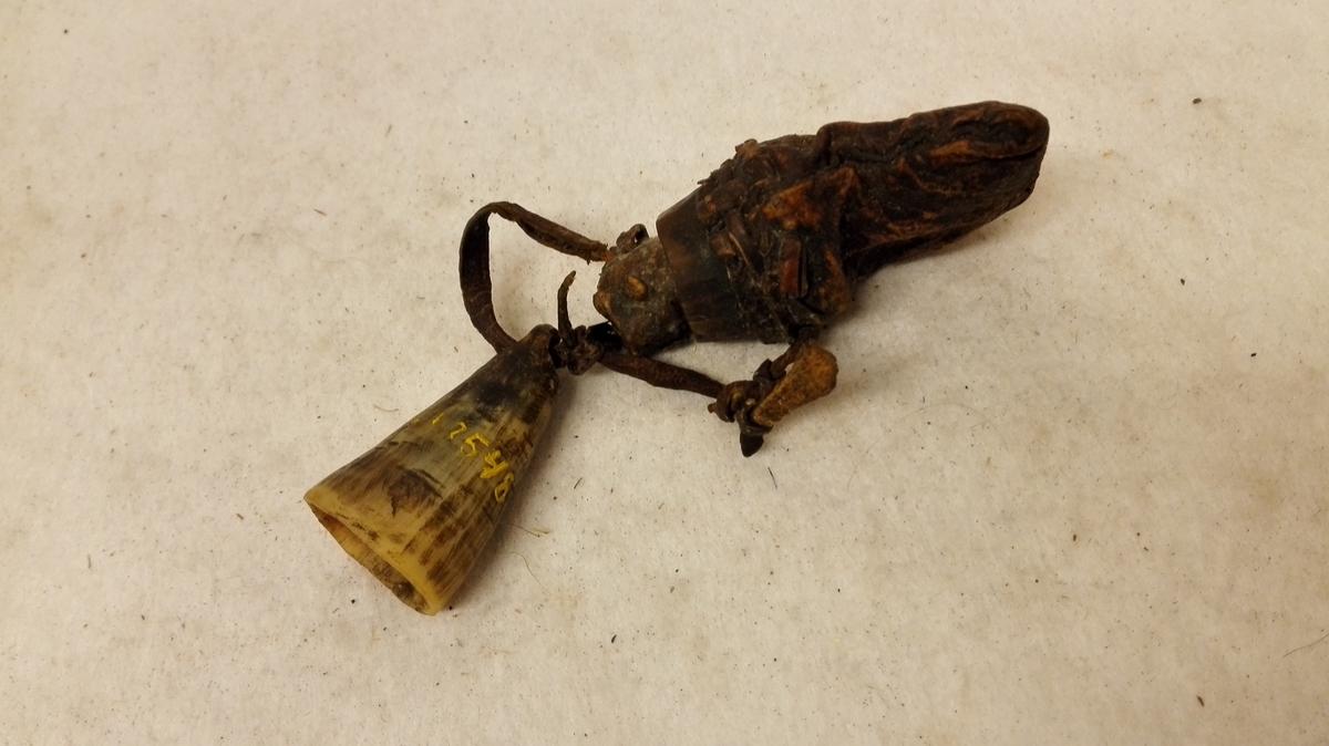 1 Kulepung med Krudtmaal  En kulepung av skind med tut av horn. I tuten en propp av sammenrullet skind. I en skindreim sydd til pungen hænger toppen (spissen) av et horn, der har tjent som krudtmaal.  Gave fra Per Husabö, Leikanger