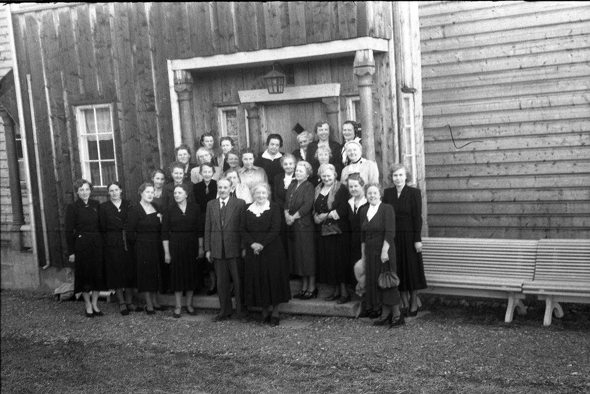 En gruppe kvinner og en mann foran inngangen til et ukjent hus. Kvinnene tilhører trolig foreningen Hoff Sykepleierforening. De arbeidet for å få helsesøster i Hoff sogn. Ble muligens senere et arbeidslag i Sanitetsforeningen. Tre identiske bilder, pluss et fjerde bilde der personene er nummerert. De fleste personene er identifisert, og nummereringen som følger er iht. bilde nr. 4 (som = nr. 1): 1.Solveig Fodstad, 2.Aase Haug, 3.Solveig Gaarder, 4.Gunvor Prestesæter, 5.Ingebrigt Hole, 6.Marie Hole, 7.Tora Enger, 8.Margit Rindal, 9.Margit Gihle, 10.Ukjent. 11.Augusta Martinsen, 12.Marta Emilie Toresen, 13.Hildur Rødset, 14.Olaug Rust, 15.Nelly Gaarder, 16.Nicoline Kobberstad, 17-21.Ukjent, 22.Signe Fodstad, 23-24.Ukjent, 25.Sigrid Anette Kvale-Hougen, 26.Tora Prestesæter, 27.Berit Wangensten, 28.Ella Eriksen.