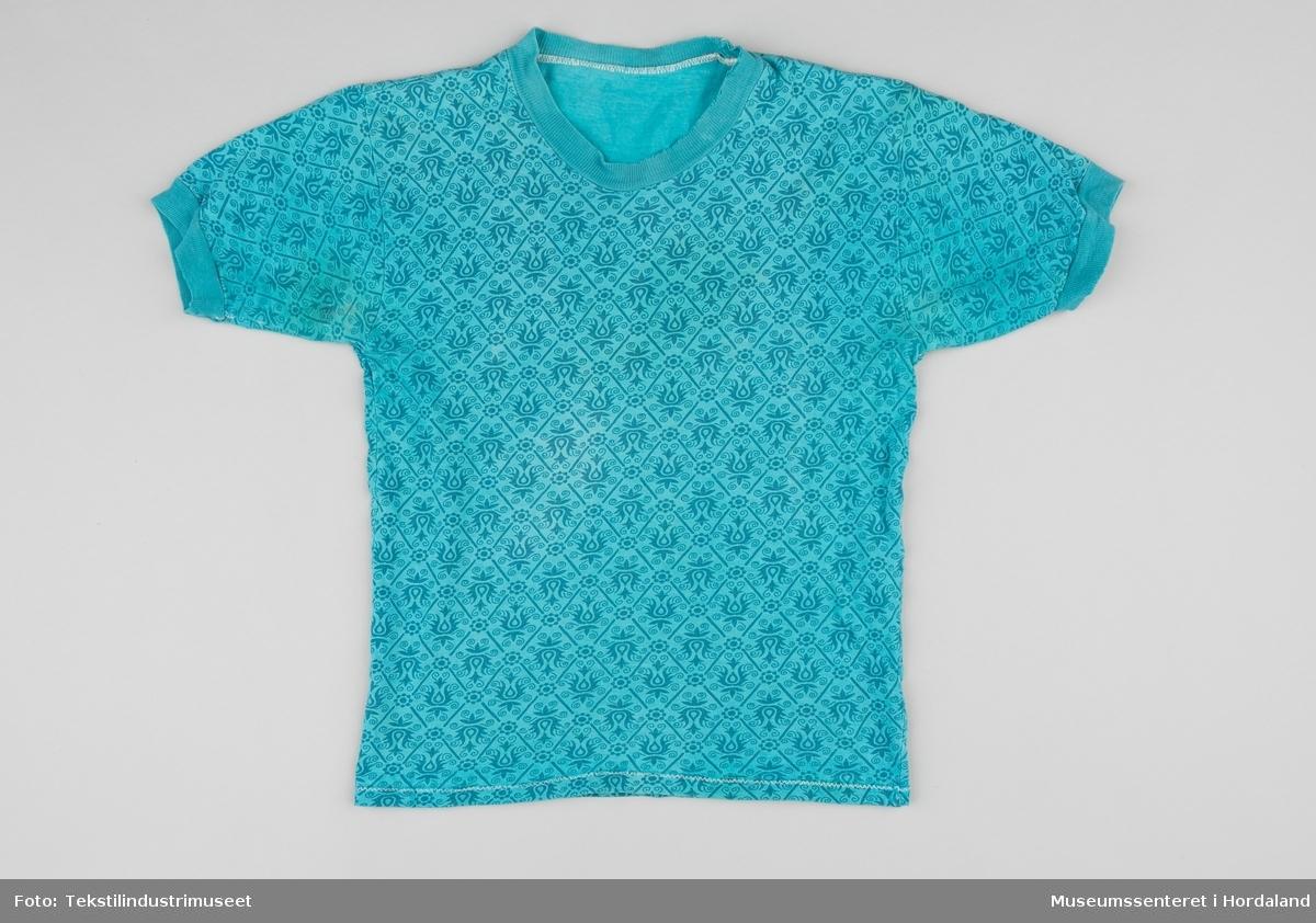 Turkis t-skjorte i barnestørrelse, med påtrykt blomstermønster.