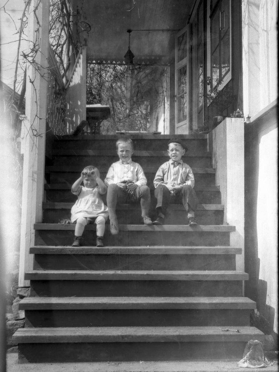 Tre barn sitter på trapp.