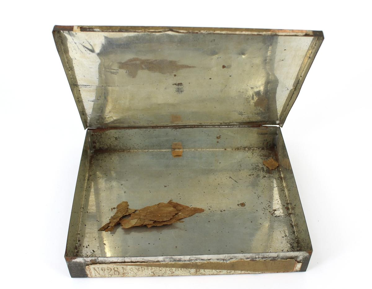 Plåtask för cigaretter. Påklistrad pappersetikett med tryck: Egyptiska cigaretter 1ma qualite P-C- Rettig & co Gefle No 28.