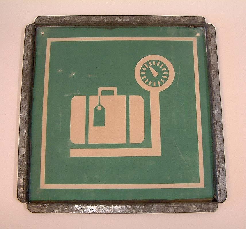 Screenram med grön väv, för tryck av skylt. Bilden visar en godsvåg med en resväska. Väven är tät, 88 st maskor /cm2. Rengöring av duken efter tryck gjordes med lacknafta.