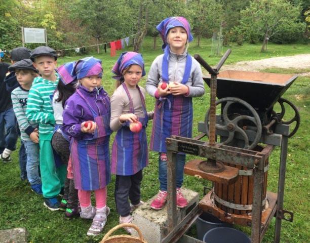 Elever i kø for å legge epler i eplepressa.