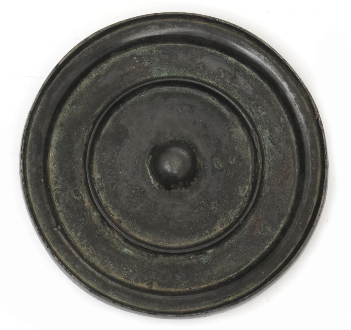 Sirkelformet speil, med en knott på midten til å holde i.  Bronsespeil er en form for speil som var i bruk før de moderne glasspeil.