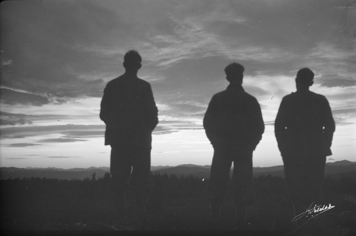 Ringebu. Tre menn i siluett betrakter Jotunheimen ved solnedgang.