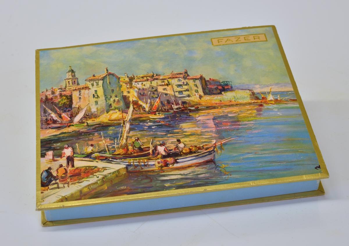 """Locket pryds av en reproduktion av en oljemålning föreställande ett fiskeläge vid Medelhavet. Text i guldrelief """"FAZER"""" inom en guldram. På askens under sida text """"OY KARL FAZER HELSINKI - HELSINGFORS. No 2484 """"Saint Tropez"""". Sis TAZERIN PARHAIN suklaa konv. Inneh FAZERS BÄSTA choklad konf. n 420 g ca"""". Ett blad brunt silkespapper ligger i asken. Asken känns tung .  Från Arne Ekströms handelsmuseum."""