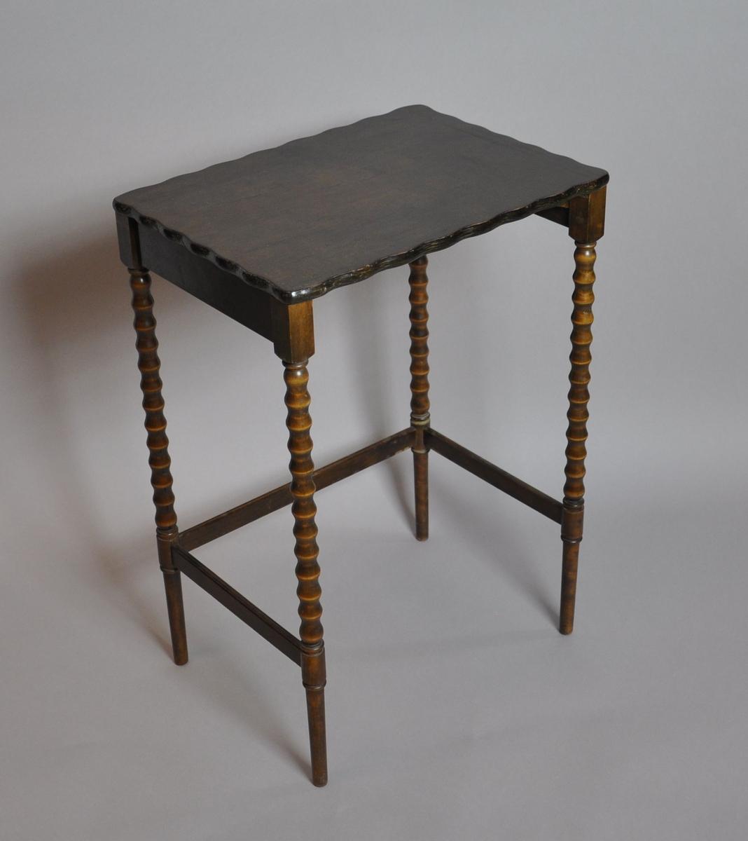 Bord av tre. Bordplaten er sveifet slik at kantene har bølgeform. Flate sarger på tre av sidene, hvorpå den ene langsiden er åpen. Står på fire bein av dreid tre. Det er sprosser mellom beina, med unntak av den ene langsiden.