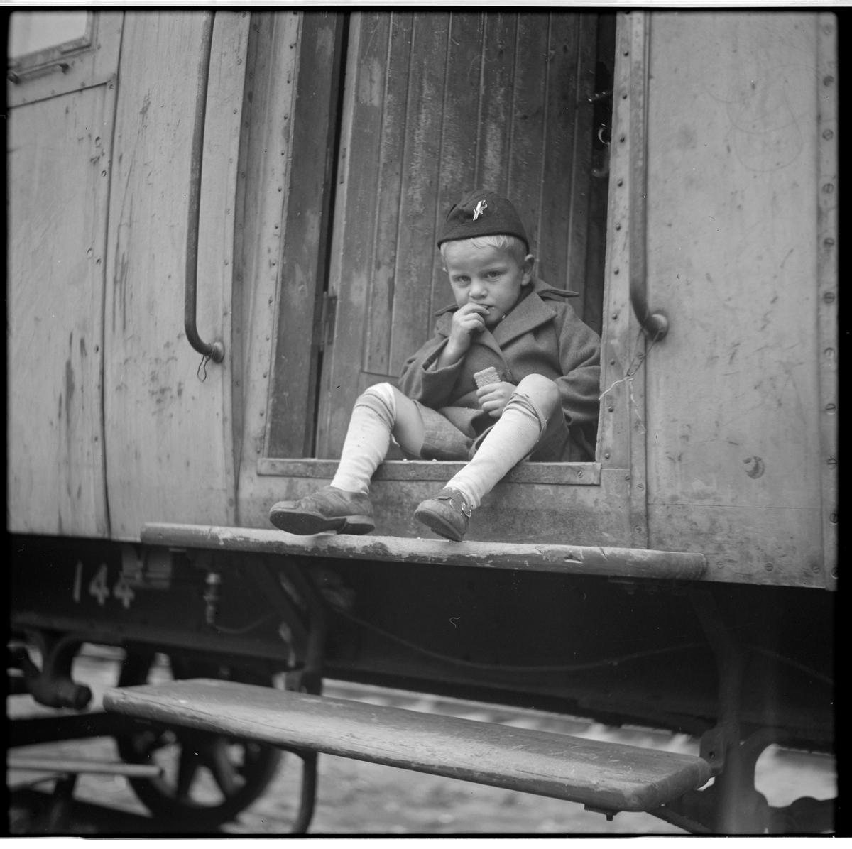 Okänd pojke sitter på avsatsen sitter till Statens Järnvägar, SJ Bostadsvagn 144.