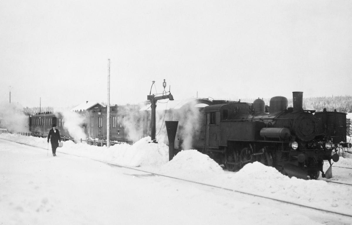 Statens Järnvägar SJ J 1401 med persontåg i Vansbro. Loket fick förenklad AGA-belysning och ångbromsen bytt mot Knorrbroms 1921. Vakuumbromsapparaterna vars slangar syns här satt kvar till 1929. Bakom loket en kyl/värmevagn litt Hs och därefter en f.d. MVJ-vagn här CDF0 2503 eller 2504. CDF0-vagnarna blev DF02 1929. Sen C3d och BC05 samt ett ångmoln som döljer en vagn till.
